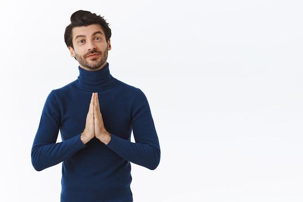 Красивый кокетливый бородатый молодой человек в синем свитере с высоким воротом, прижатый ладонями к груди в молитвенном жесте, улыбаясь, благодарит кого-то, просит совета или помощи, стоит у белой стены
