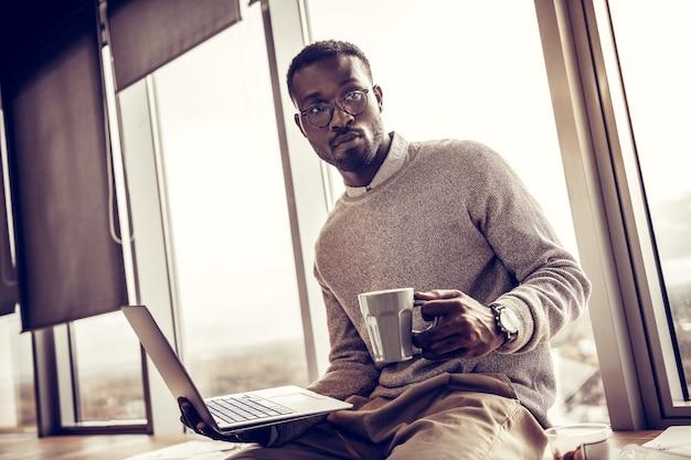ハンサムなフリーランサー。窓辺に座っている間、右手にラップトップを保持している陽気な男性