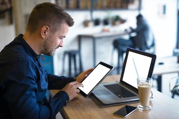 タブレットとラップトップコンピューターを使用してカフェで彼のビジネスをチェックするハンサムなフリーランサー