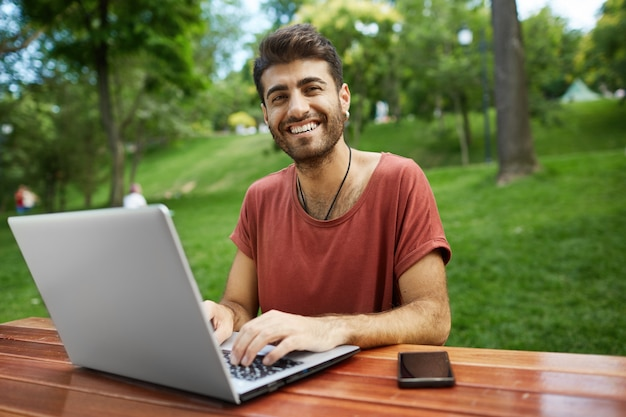 원격 작업 잘 생긴 프리랜서, 노트북과 공원 벤치에 앉아, 와이파이 연결