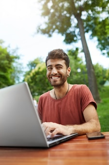 Handsome freelancer working remote, sit on park bench with laptop, connect wifi