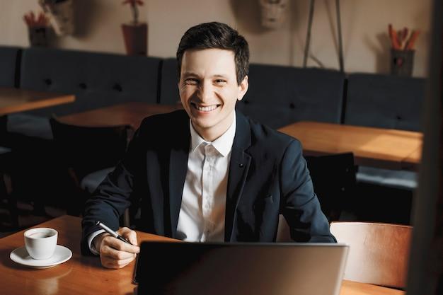 笑顔でカメラを見ながらコーヒーを飲みながら喫茶店に座って働くハンサムなフリーランサー。