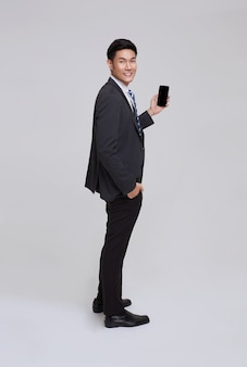 Handsome and friendly face asian businessman smile in formal suit his using smartphone on white background studio shot.
