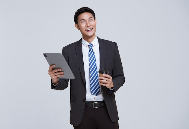 Handsome and friendly face asian businessman smile in formal suit his using tablet on white background studio shot.