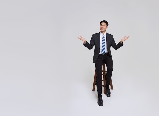 Handsome and friendly face asian businessman smile in formal suit points his hands to presented to copy space on white background studio shot.