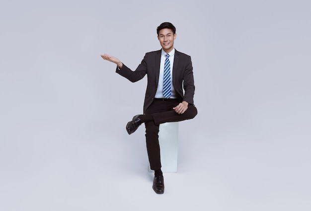 Handsome and friendly face asian businessman smile in formal suit sitting on chair points his hands to presented on white background studio shot.