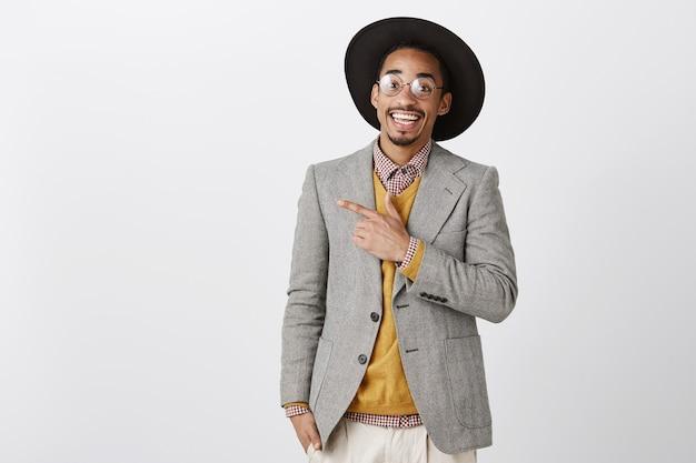 Bello dall'aspetto amichevole uomo afro-americano che punta il dito nell'angolo superiore sinistro