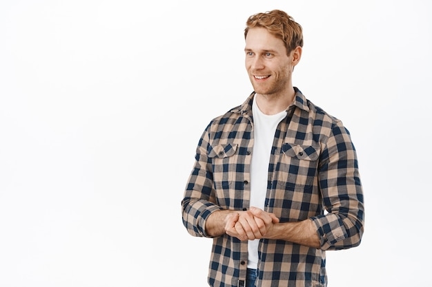Handsome friendly-looking redhead man, holding hands together in polite poses, smiling and looking aside at client or customer, offer his assistance, helping you, standing over white wall