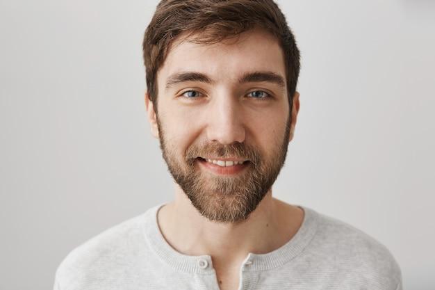 Красивый дружелюбный улыбающийся мужчина с бородой