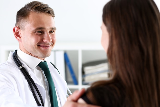 Handsome friendly male doctor talk with thankful female patient