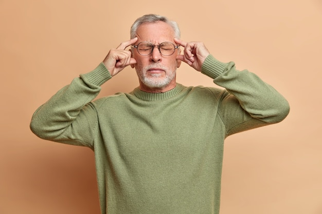 Handsome frustrated man has terrible migraine keeps hands on temples closes eyes to reveal pain stands tired wears glasses and sweater isolated over brown wall