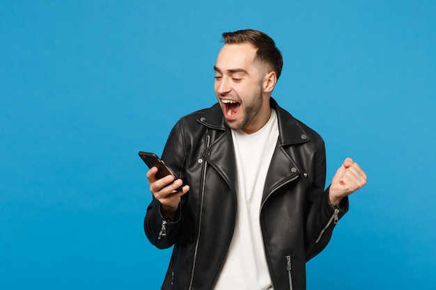 Handsome fun overjoyed excited young unshaven man in black leather jacket white t-shirt using mobile phone isolated on blue wall background studio portrait. people lifestyle concept mock up copy space