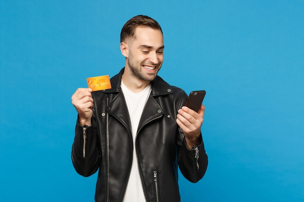 Handsome fun stylish young unshaven man in black jacket white t-shirt hold in hand cellphone, credit card isolated on blue wall background studio portrait. people lifestyle concept. mock up copy space