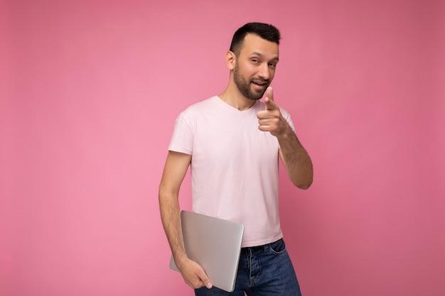 노트북 컴퓨터를 들고와 격리 된 분홍색 벽에 티셔츠에 당신을 가리키는 잘 생긴 재미 brunet 남자.