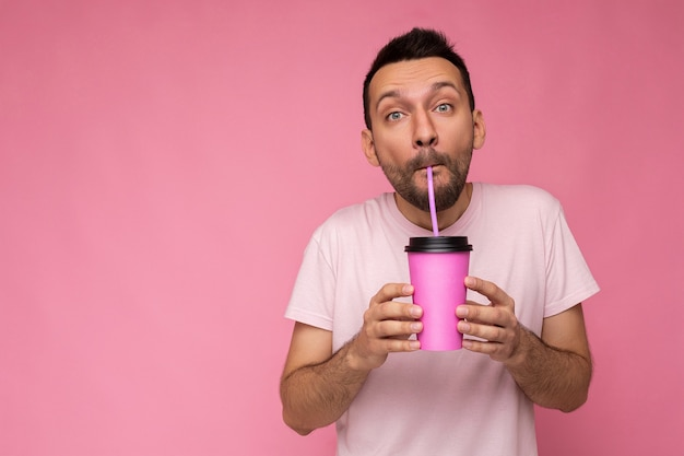 Handsome funny joyful young brunette unshaven male person with beard wearing white t-shirt isolated over pink wall holding paper cup drinking and enjoying. copy space