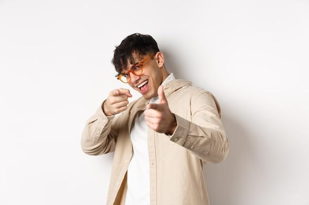 Красивый забавный человек в очках улыбается, указывая пальцами на камеру, выбирает или приглашает вас, стоя на белом фоне