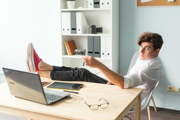 白いシャツを着たハンサムな面白い男は、オフィスに座って休んでいます