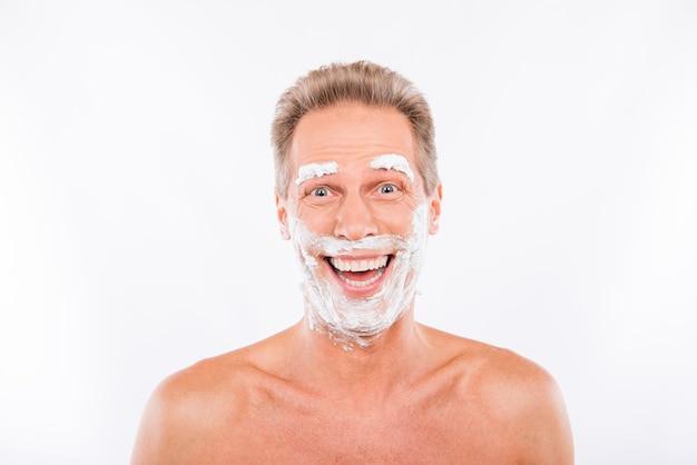 あごと眉毛に泡を剃っているハンサムな面白い男