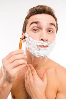 Красивый забавный мужчина с пеной для бритья на лице и бритвой