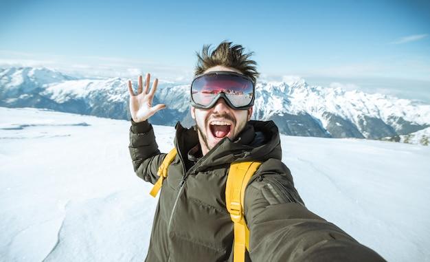 Красивый смешной лыжник принимает селфи в зимнее время в снегу на горе