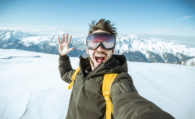 Handsome funny skier is taking a selfie at wintertime in the snow on a mountain