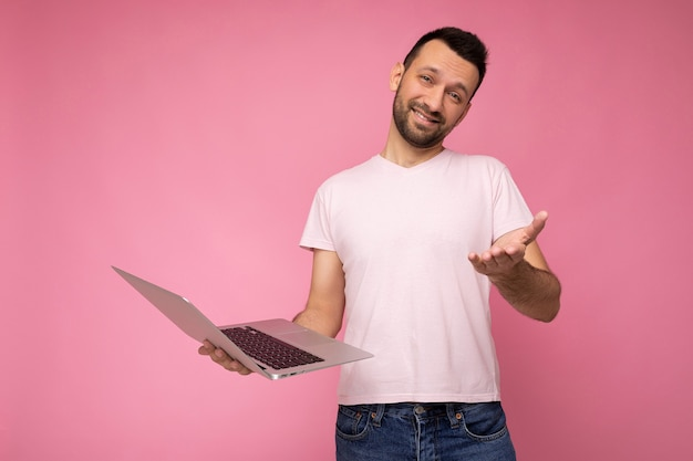 Handsome funny and smiling brunet man holding laptop computer and showing hand  in t-shirt on isolated pink wall.