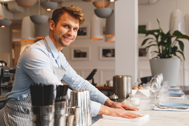 Handsome gentleman in apron looking and smiling while placing hands on countertop