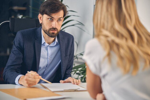 Handsome gentleman communicating with female business partner while sitting at the table with clipboard