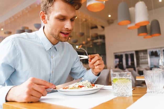 테이블에 앉아 카페에서 맛있는 신선한 샐러드를 먹는 잘 생긴 신사