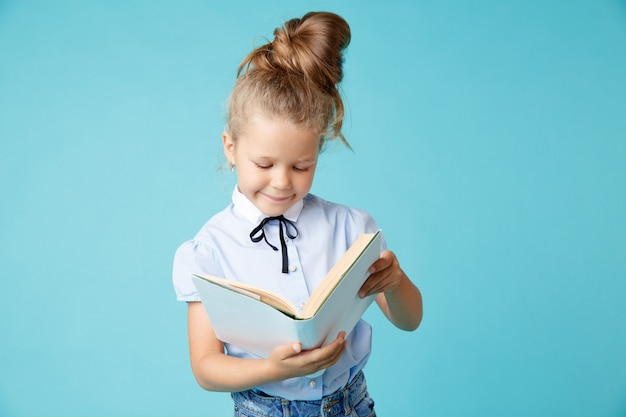 青い部屋で手に白い本を持っているハンサムな女の子。