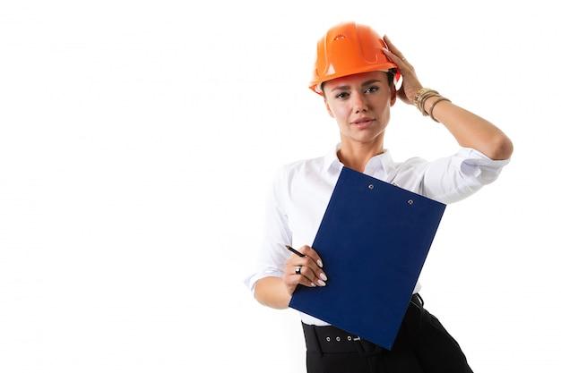 Красивая девушка в строительной каске с документами в руках на белом фоне