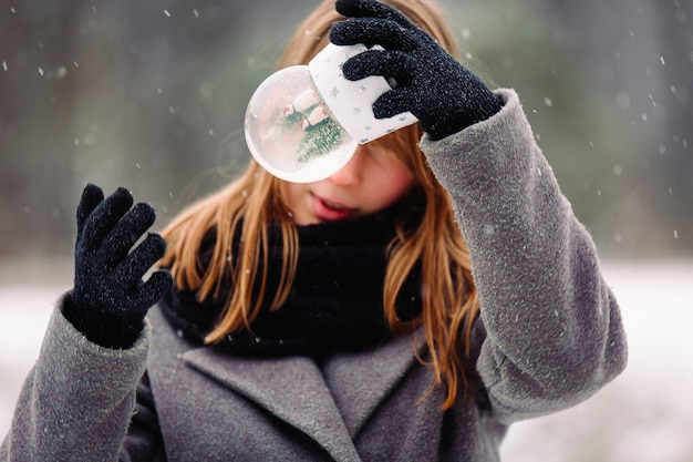 A handsome girl in surprise shakes a glass winter snow globe in front of her face. enlarged photo of