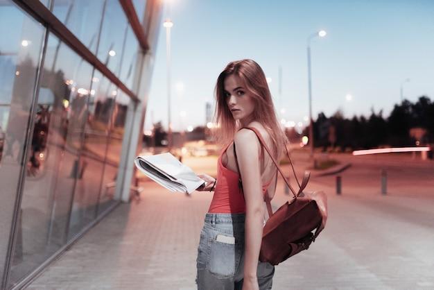 공항 건물 근처를 걷고 정면을 보면서지도를 들고 잘 생긴 소녀