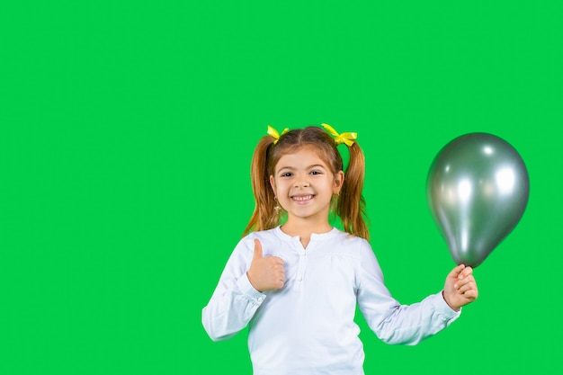 Красивая девушка с искренней улыбкой и воздушным шаром показывает большой палец вверх