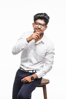 Handsome good looking indian man sitting on a chair and relaxing, isolated for white wall