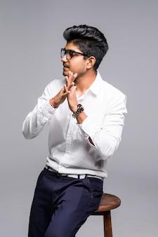 Красивый красивый индийский мужчина сидит на стуле и расслабляющий, изолированных на белой стене
