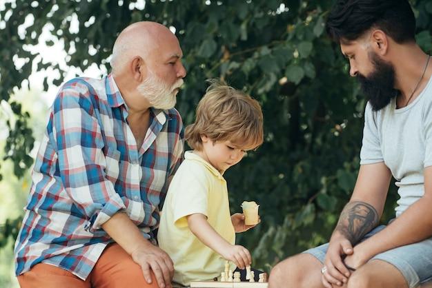 ハンサムなおじいちゃんと孫が屋外で一緒に時間を過ごしながらチェスをしています
