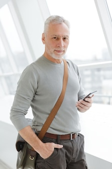 Handsome gray-haired man with bag typing on cellphone while standing near windows indoors