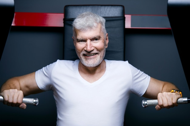 マシンジムでハンサムな白髪の年配の男性。スポーツとヘルスケアの概念