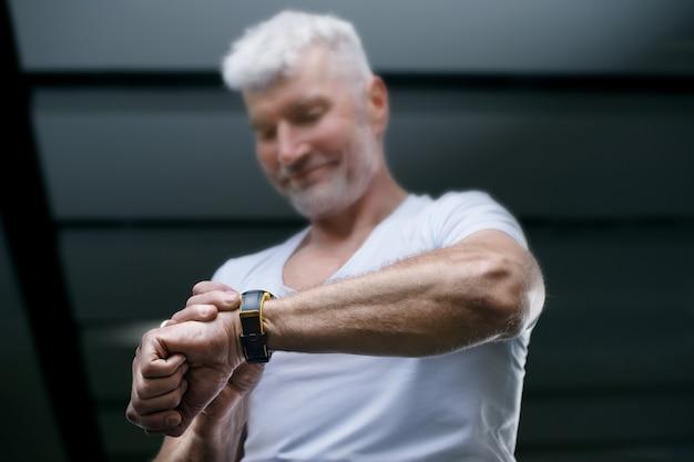 彼の手でスポーツ時計を見ているハンサムな白髪の年配の男性。スポーツとヘルスケアの概念