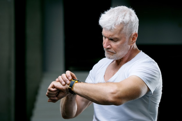 Handsome gray haired senior man looking at sport watch at his hand sport and health care concept