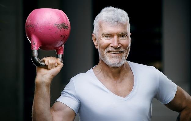彼の手にピンクのケトルベルの重みを持つハンサムな白髪の年配の男性。スポーツとヘルスケアの概念