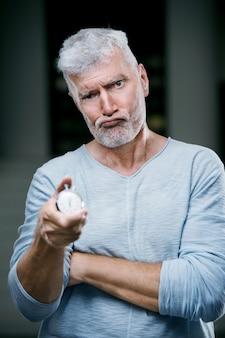 彼の手にストップウォッチの重みを持つハンサムな白髪の年配の男性。スポーツとヘルスケアの概念