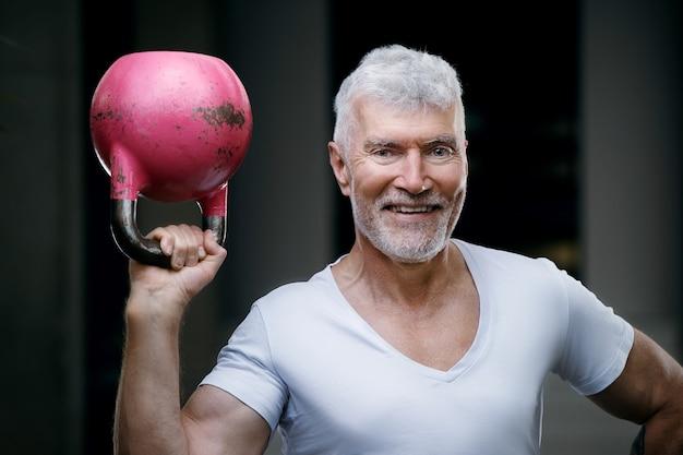 ピンクのケトルベルの重みを持つハンサムな白髪の年配の男性。スポーツとヘルスケアの概念