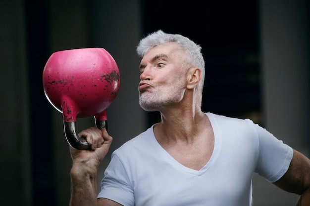 Handsome gray haired senior man with pink kettlebell weight. sport and health care concept