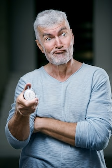 Handsome gray haired senior man with a stopwatch weight in his hand. sport and health care concept