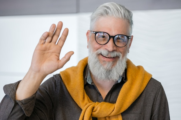 Handsome grayhaired adult man portrait of a business man in a dark shirt and yellow sweater