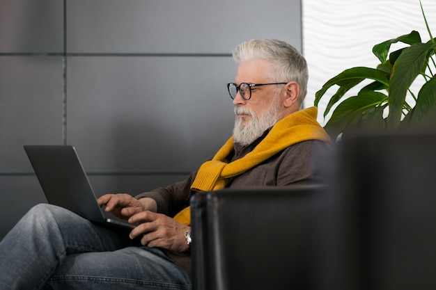 Handsome grayhaired male director or top manager working with a laptop and chatting online
