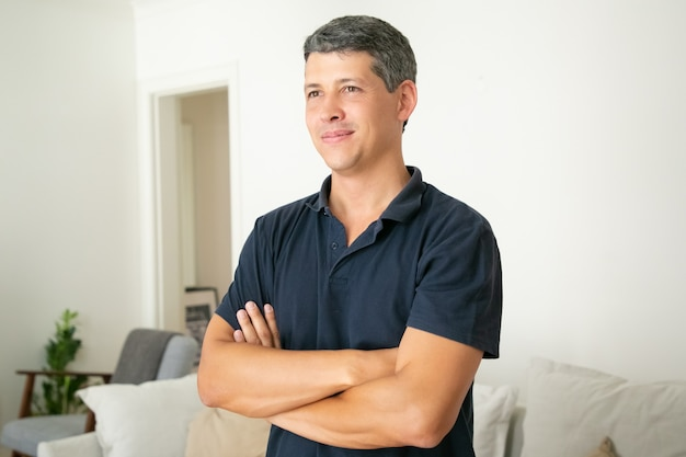 Handsome grey-haired man standing with folded hands, smiling and looking away.