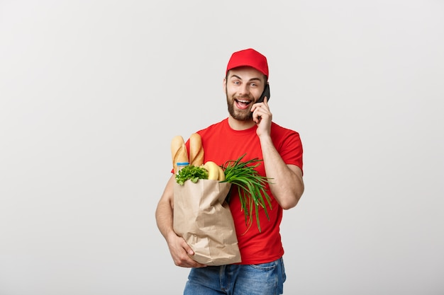 Handsome grocery delivery man talking to mobile and holding grocery paper bag.